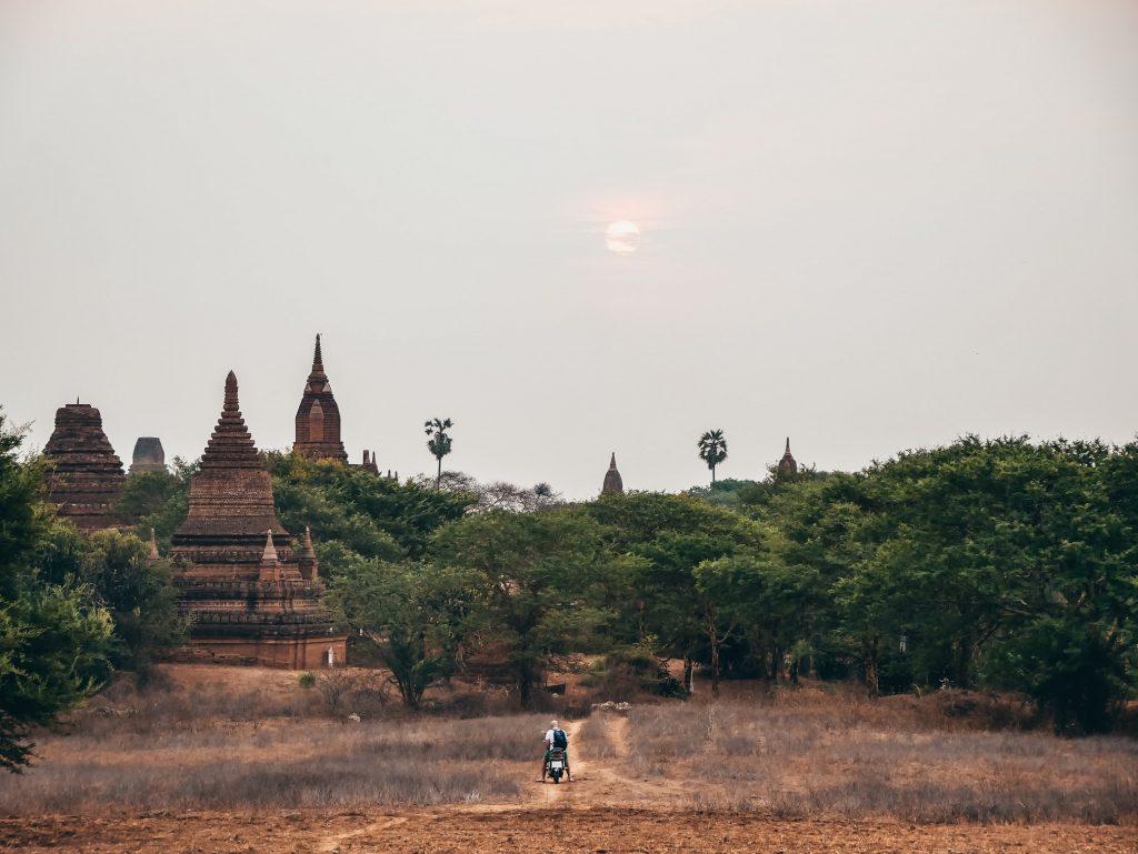 chico en moto recorriendo los templos Bagan un día nublado