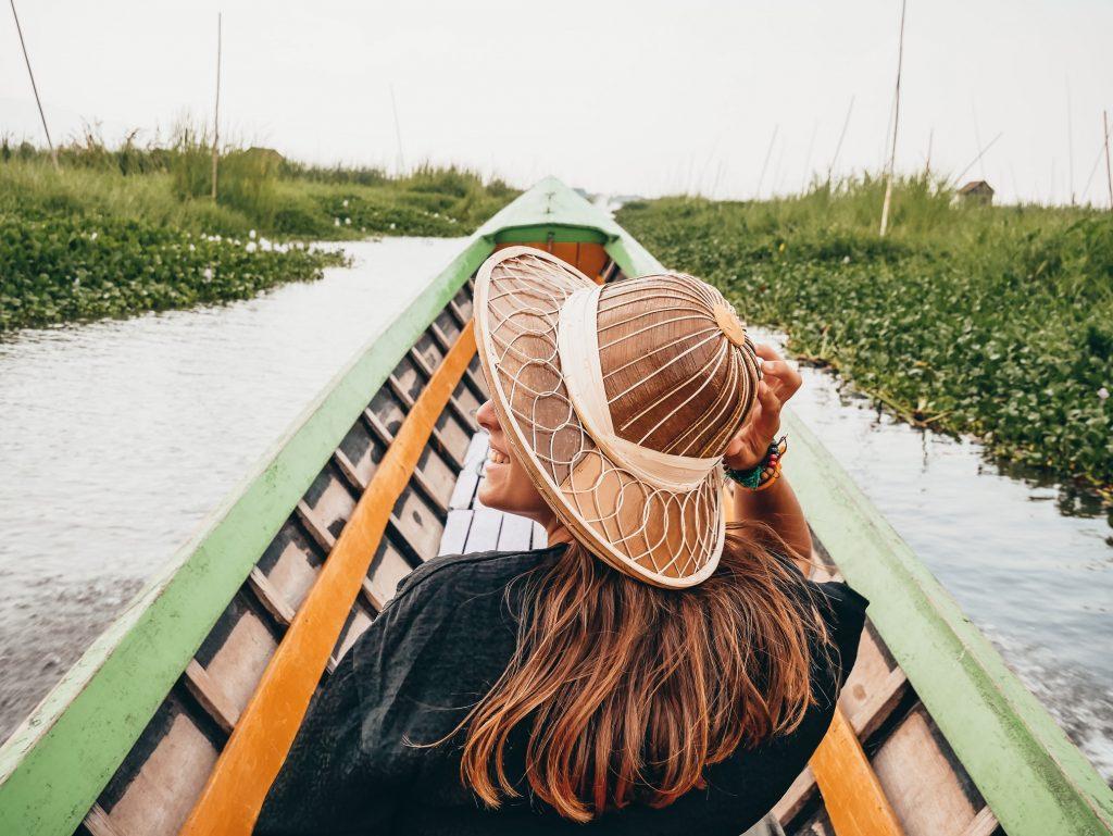 chica posando subida a una barca en el lago Inle