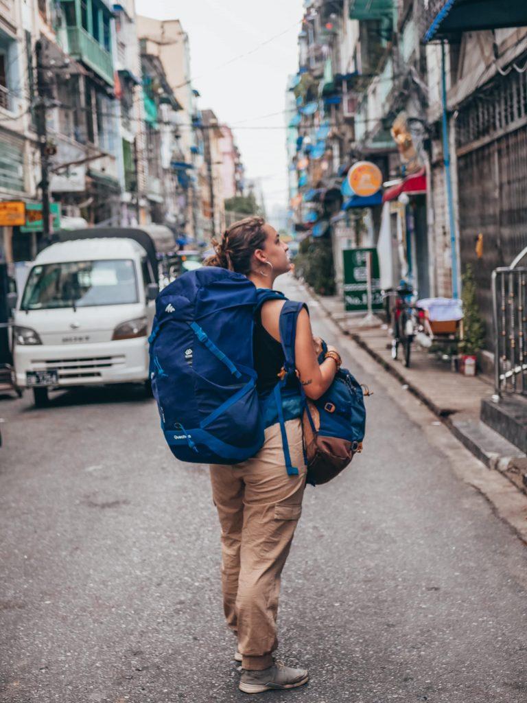 chica con mochilas en una calle de Yangón