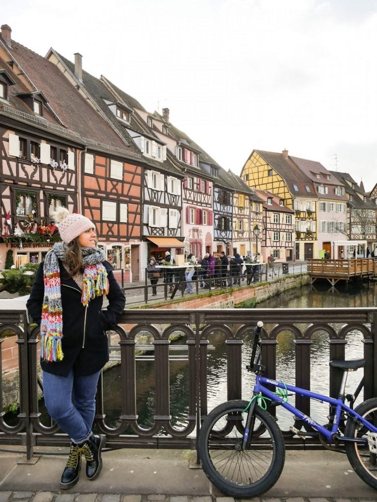 chica posando delante de las casas de colores del Colmar