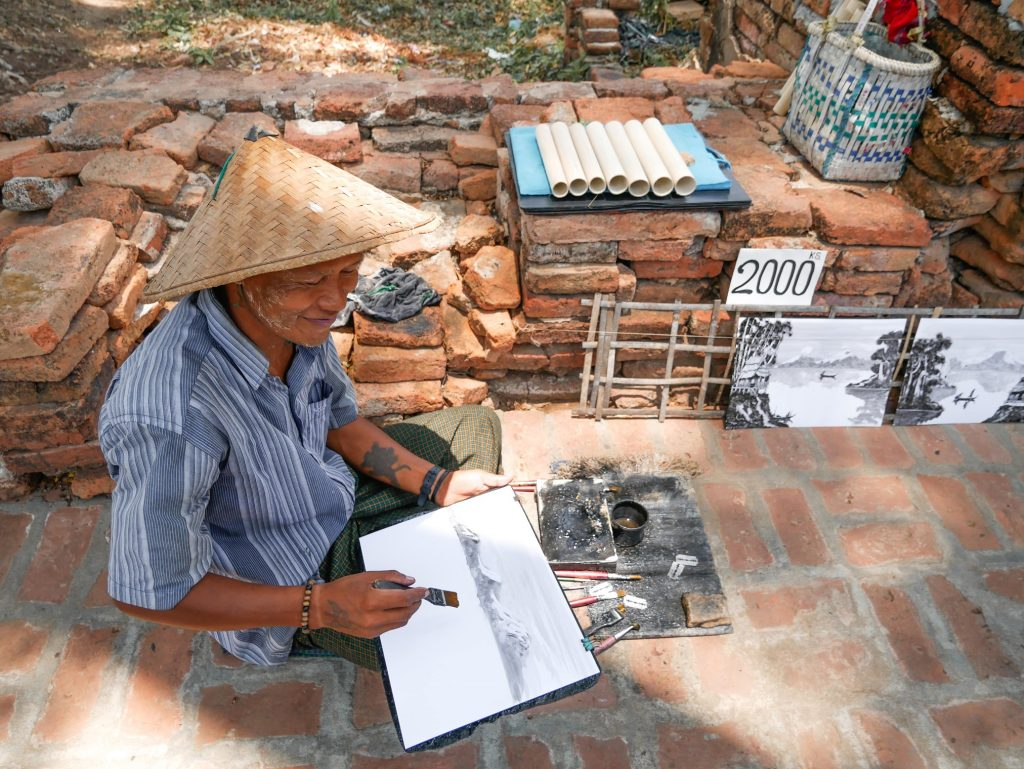 birmano dibujando láminas para lueego vender como souvenirs en Myanmar